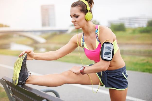 屋外で運動する若い女性。怪我をしないようにストレッチをする 無料写真