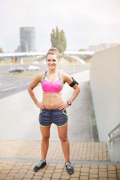 屋外で運動する若い女性。階段に立っているジョガー女性の肖像画 無料写真