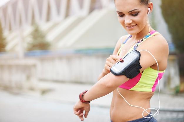 屋外で運動する若い女性。このガジェットはジョギング中にとても役立ちます 無料写真