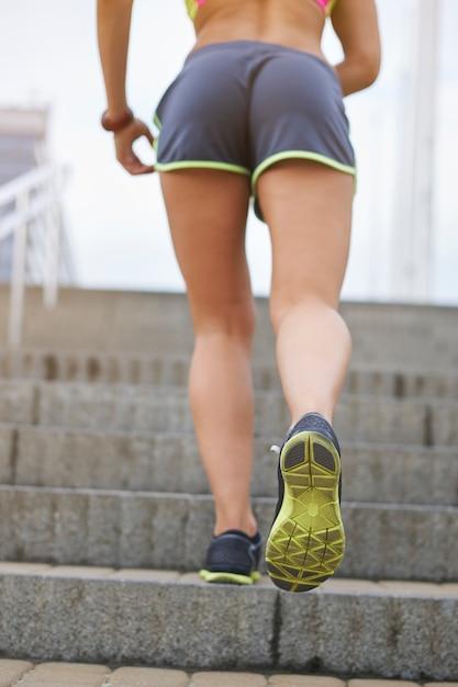 야외 운동하는 젊은 여자. 도시의 단계에서 실행하는 여자 무료 사진