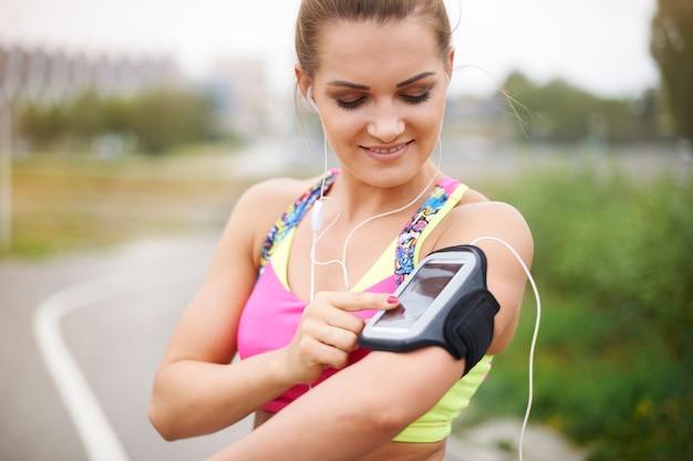 外で運動する若い女性。ジョギングの前にプレイリストをオンにする 無料写真