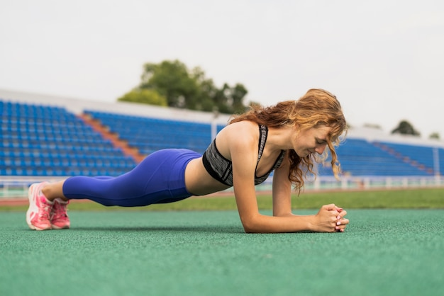 Young woman exercising at stadium Free Photo