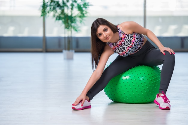 Young woman exercising with swiss ball in health concept Premium Photo
