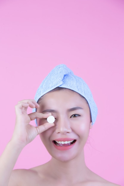 Young woman face mask pad pink background. Free Photo