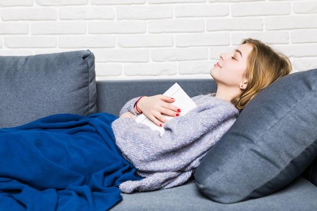 Giovane donna addormentata durante la lettura sdraiata sulla schiena nel letto con il suo libro appoggiato sullo stomaco Foto Gratuite