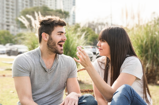Young woman feeding strawberry to her boyfriend in the park Free Photo