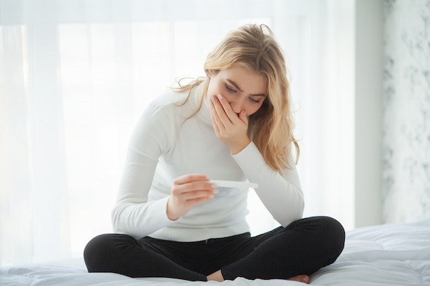 Young woman feeling depressed and sad after looking at pregnancy test result at home Premium Photo