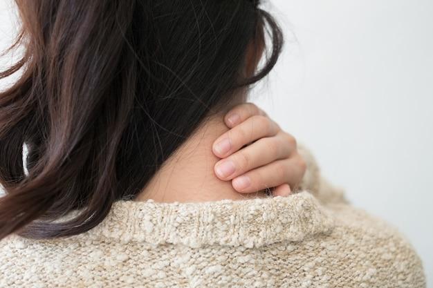 Молодая женщина чувствуя вымотанный и страдающий от боли в шее, концепции здоровья. Premium Фотографии