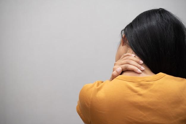 Молодая женщина чувствует себя истощенной и страдающей от боли в шее Premium Фотографии