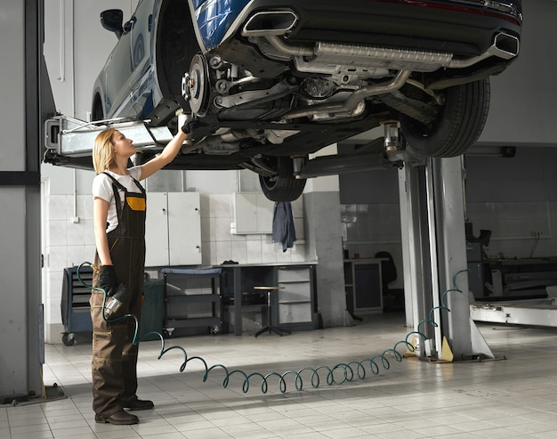 Young woman female mechanic checking chassis in workshop Free Photo
