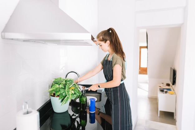 Young woman filling water in sauce pan in the kitchen Free Photo