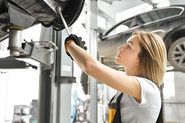 Young woman fixing car undercarriage in autoservice. Free Photo