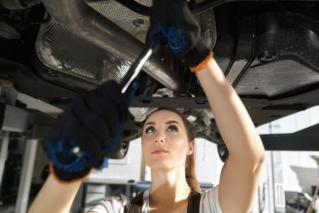 Young woman fixing undercarriage with wrench. Free Photo
