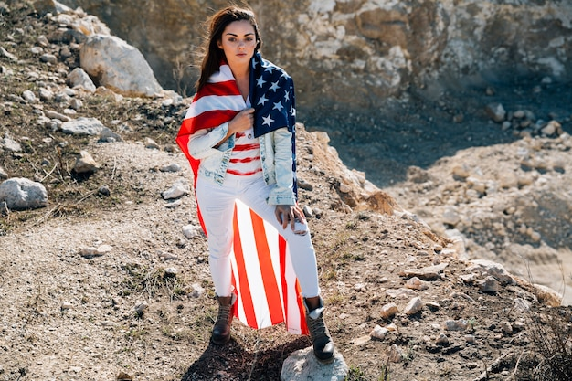Young woman in flag standing on mountain Free Photo