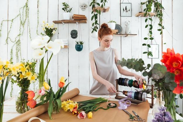 Флорист молодой женщины делает букет с цветами и лентами Бесплатные Фотографии