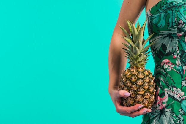 Young woman in flowered dress holding pineapple Free Photo