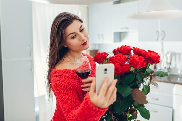 Молодая женщина нашла букет роз на кухне. счастливая девушка принимая selfie на телефоне пить вино. сюрприз ко дню святого валентина Premium Фотографии