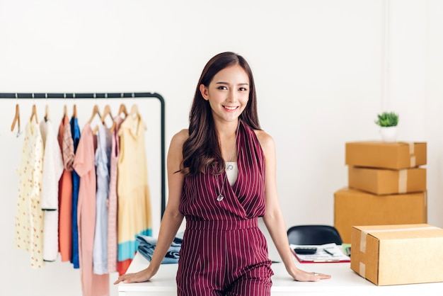 Young woman freelancer business online shopping look at camera with cardboard box on table at home. business online shipping and delivery concept Premium Photo