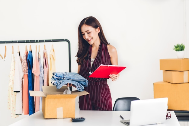 Young woman freelancer working sme business online shopping and packing clothes with cardboard box at home - business online shipping and delivery concept Premium Photo