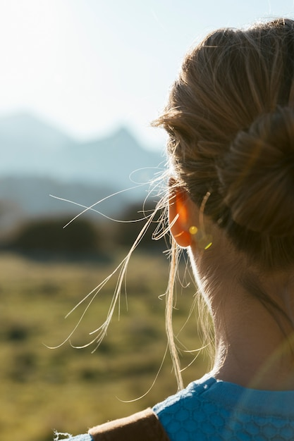 Young woman from behind facing sun Free Photo