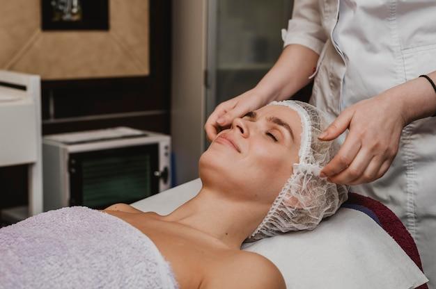 Giovane donna che ottiene un trattamento cosmetico Foto Gratuite