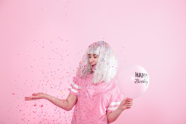 Young woman or girl with balloons happy birthday. throws confetti from above. holiday and party concept. Free Photo