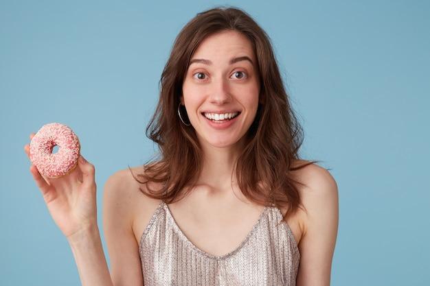 手に持つ甘いピンクのドーナツを食べに行く若い女性 無料写真