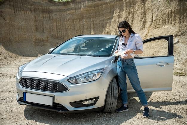 若い女性は道に迷い、新しい旅行を計画するために地図を探していました。車の近くの道路に立っている女性 Premium写真
