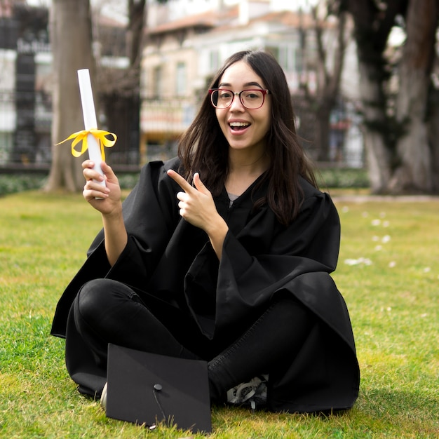 Young woman at graduation ceremony pointing to her diploma Free Photo