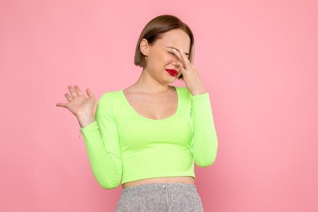 Giovane donna in camicia verde e gonna grigia che ha problemi con l'odore puzzolente Foto Gratuite