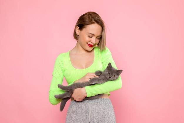 Giovane donna in camicia verde e gonna grigia che tiene carino gattino grigio Foto Gratuite