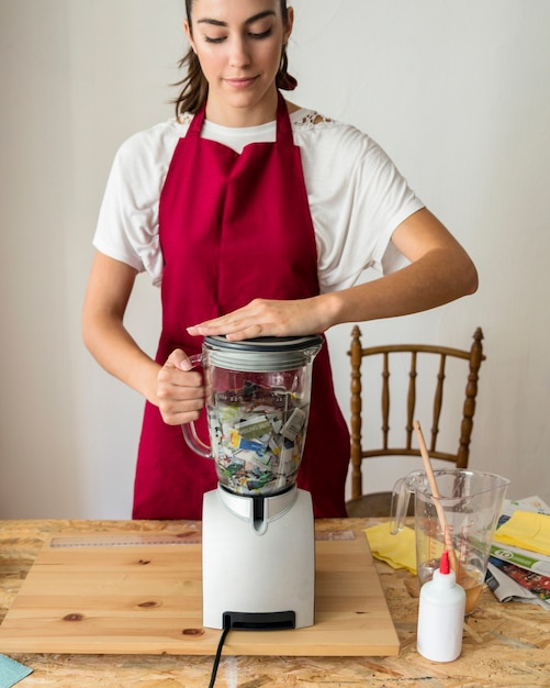 Young woman grinding torned paper in mixer grinder Free Photo