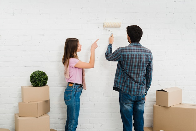 Young woman guiding his husband painting the wall with paint roller Free Photo