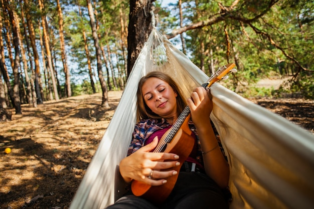 Young woman in hammock playing quitar Free Photo