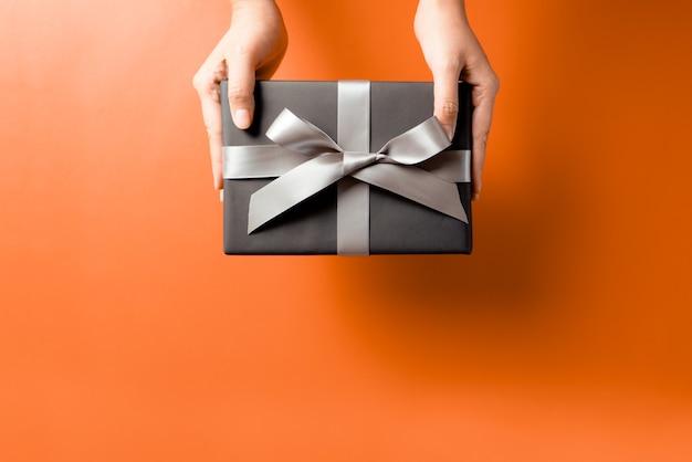 수신기에 선물 상자 제공 젊은 여자 손 프리미엄 사진