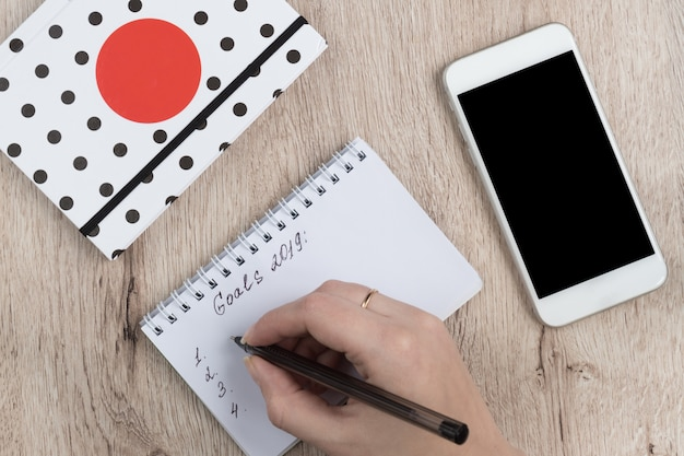 Young woman hands hold opened notebook pages with black pen on  wooden table. goals 2019 list. Premium Photo