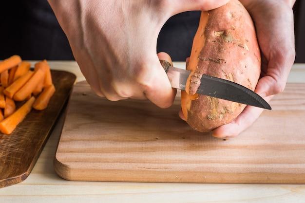 Молодая женщина руки пилинг с ножом сладкий картофель над деревянной разделочной доской Premium Фотографии