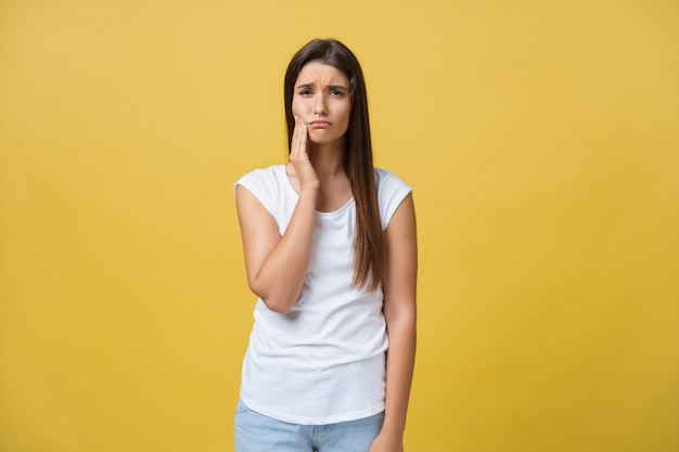 Young woman has a toothache, studio photo isolated on a yellow background Premium Photo