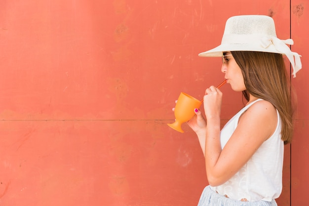 Young woman in hat holding cup and drinking through straw Free Photo