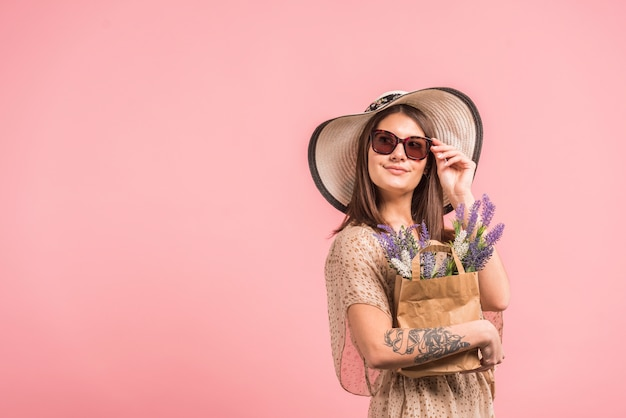 Young woman in hat and sunglasses holding bag with flowers Free Photo