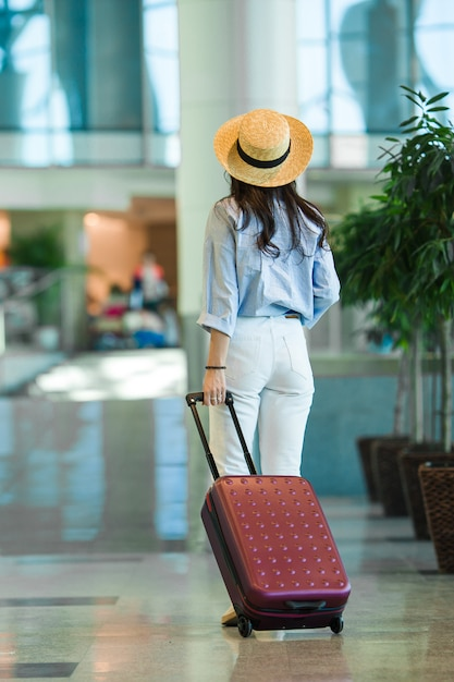 Young woman in hat with baggage in international airport walking with her luggage. Premium Photo