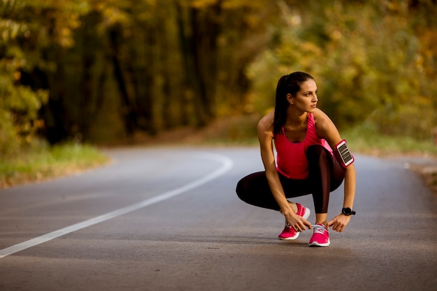 Young woman have a break during training in the autumn forest Premium Photo