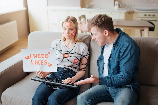 若い女性はソーシャルメディア中毒があります。感情のないソファに座っています。本体はコードで包まれています。キーボードの手。怒っている若い男が叫んでいます。感情的な人々。 Premium写真