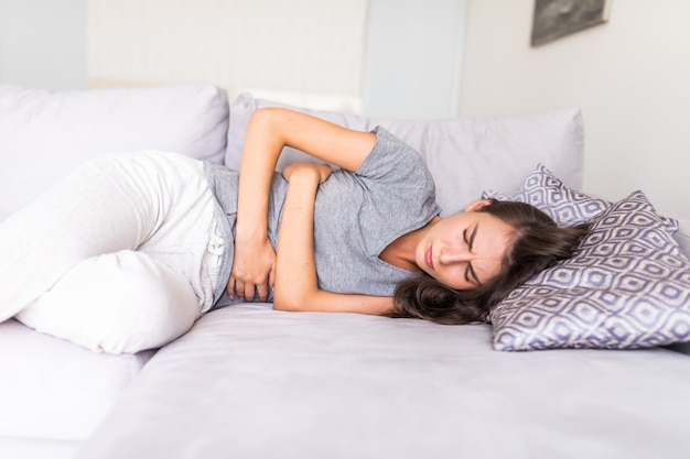Young woman haviing abdominal pain because of menstruation lying in couch and holding her stomach. Free Photo