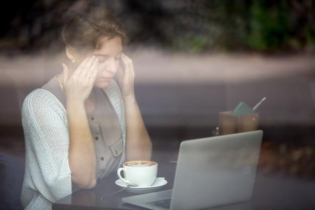 Young woman having headache. shot through window Free Photo