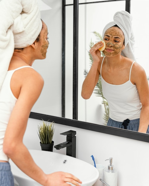 Young woman having a homemade mask on her face Free Photo