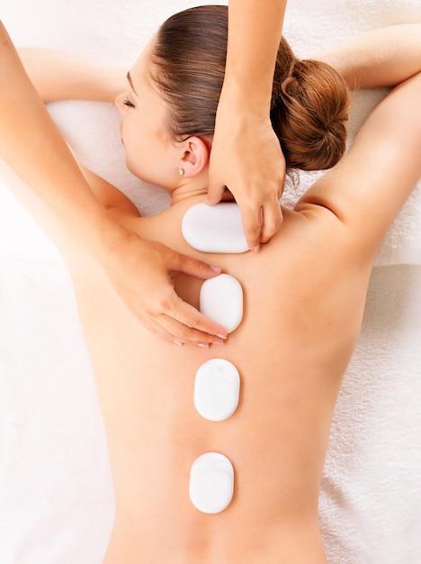 Giovane donna con massaggio con pietre calde nel salone della stazione termale. concetto di trattamento di bellezza. Foto Gratuite