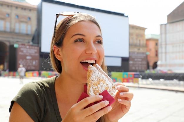 夏の路上のカフェでクロワッサンとコーヒーとイタリアの朝食を持つ若い女性 Premium写真