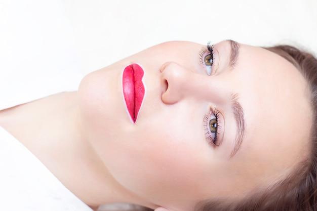 Молодая женщина с перманентным макияжем на губах в салоне косметолога Premium Фотографии
