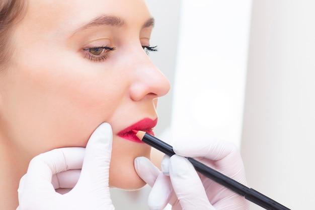 Молодая женщина, имеющая перманентный макияж на губах в салоне косметологов. перманентный макияж прорисовка контура белым карандашом для губ Premium Фотографии
